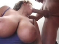 Une bonne femme blonde a gros seins suce deux grosses bites
